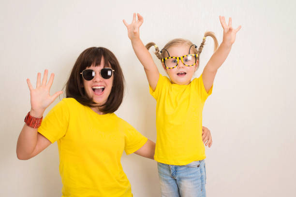 Portrait funky verrückt Hipster Mädchen in lustigen Brillen und gelben T-Shirts lachen offenen Mund Spaß zusammen. – Foto
