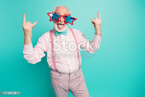 Portrait funky crazy retired gentleman make horned symbol enjoy, heavy metal concert show tongue out have vintage blue starred specs wear pink grey pants isolated turquoise color background