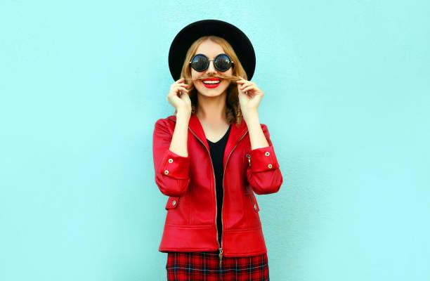 Porträt lustige lächelnde Frau zeigt Schnurrbart ihre Haare in schwarz runden Hut, rote Jacke auf blauem Hintergrund – Foto