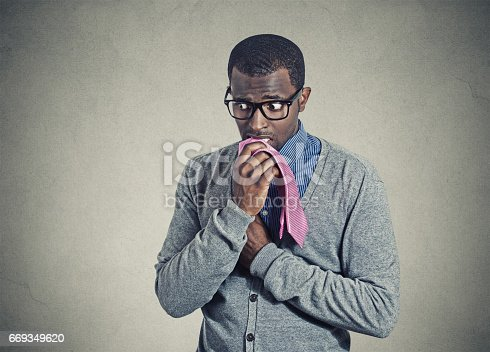 istock Portrait geeky nervous anxious businessman bitting chewing his tie 669349620