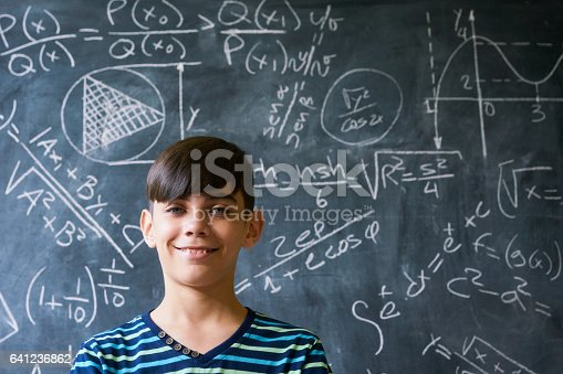 istock Portrait Genius Boy Smiling At Camera During Math Lesson 641236862