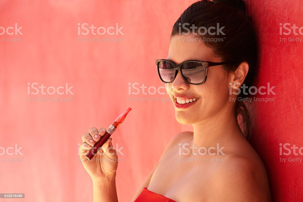 Portrait Girl Smokes Electronic Cigarette E-Cig Against Red Back stock photo
