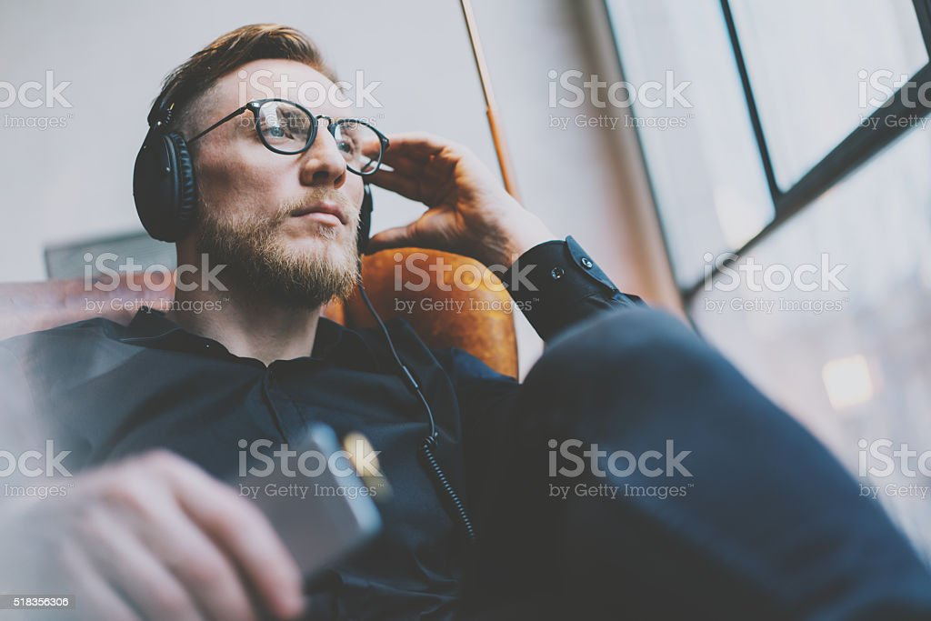 Portrait handsome bearded man glasses,headphones listening to music modern stock photo