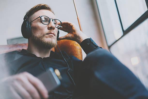 Portrait handsome bearded man glasses,headphones listening to music modern stock photo