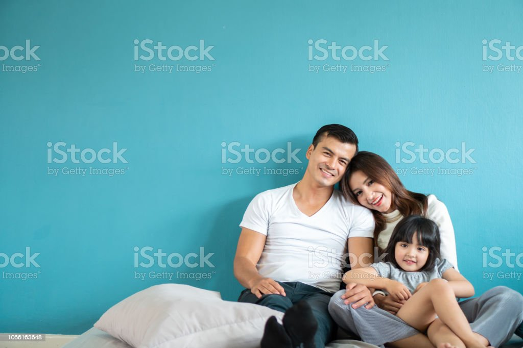 Portrait happy Asian family over blue background stock photo