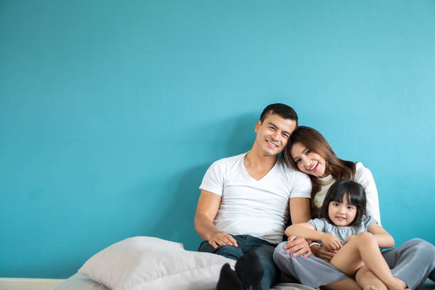 portrait happy asian family over blue background - ásia imagens e fotografias de stock