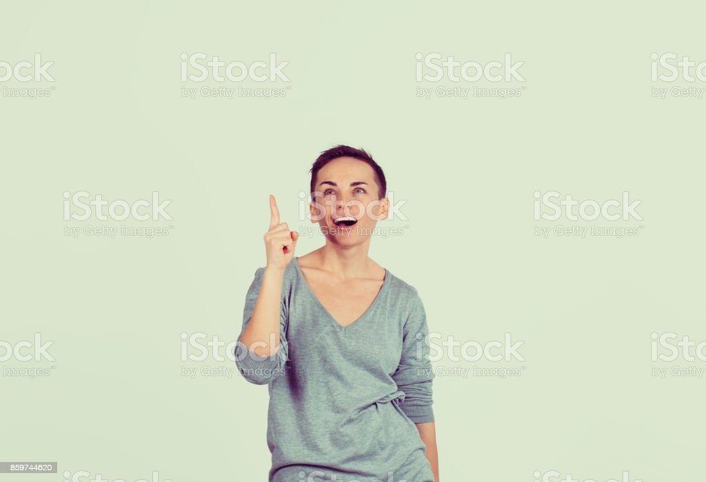 Portrait happy beautiful woman thinking looking up pointing with finger at blank copy space isolated green grey white background Positive human face expression emotion feeling body language perception stock photo