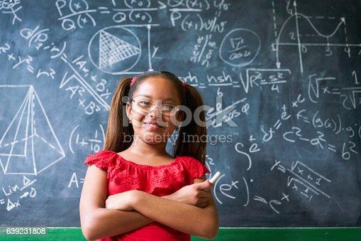 641236862 istock photo Portrait Happy Girl Resolving Complex Math Problem On Blackboard 639231808
