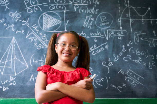 Portrait Happy Girl Resolving Complex Math Problem On Blackboard stock photo