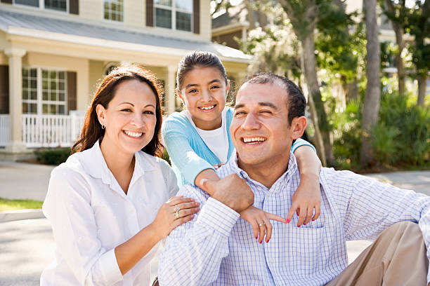 Portrait happy Hispanic family sitting with house in background stock photo