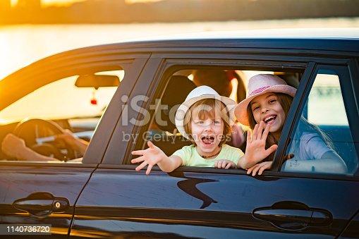 972962180istockphoto Portrait happy kids at car window 1140736720