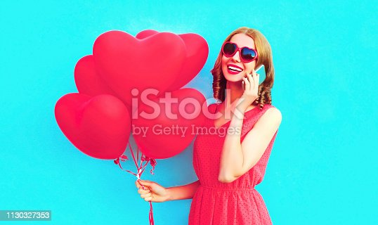 istock Portrait happy laughing woman calling on smartphone with pink heart shaped air balloons on colorful blue background 1130327353