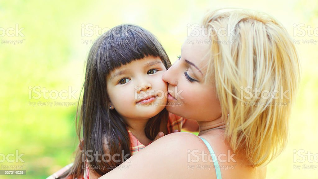 Portrait Happy Loving Mother Kissing Child Outdoors In