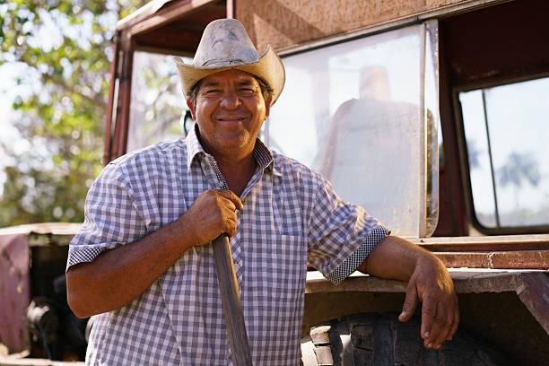 Porträt glücklich Mann Landwirt gegen Traktor schaut an die Kamera – Foto