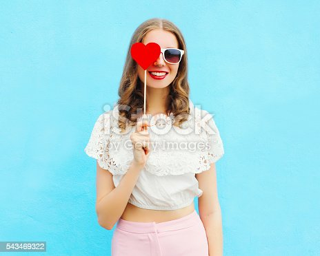 529664088istockphoto Portrait happy pretty smiling woman and lollipop over colorful blue 543469322