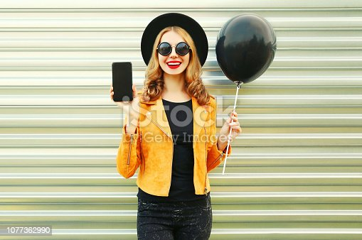 istock Portrait happy pretty smiling woman showing phone with blank screen holding black helium air balloon in round hat, yellow jacket on metal wall background 1077362990
