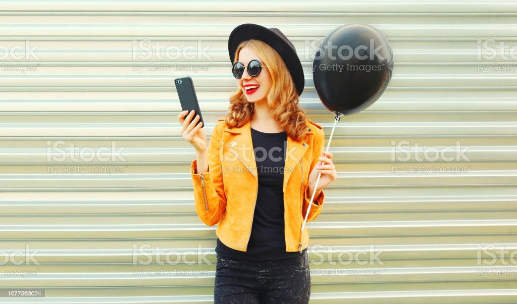Portrait happy pretty smiling woman with phone holding black helium...