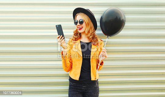 istock Portrait happy pretty smiling woman with phone holding black helium air balloon in round hat, yellow jacket on metal wall background 1077363024