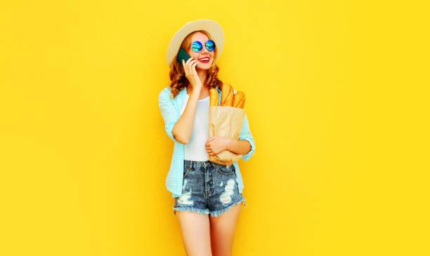 Porträt glücklich lächelnde Frau, die auf Smartphone hält Papiertasche mit langem weißen Brot Baguette, trägt Strohhut, Shorts auf bunten gelben Hintergrund – Foto