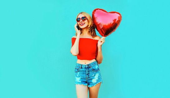 istock Portrait happy smiling woman calling on smartphone holding red heart shaped air balloon on colorful blue background 1141445304