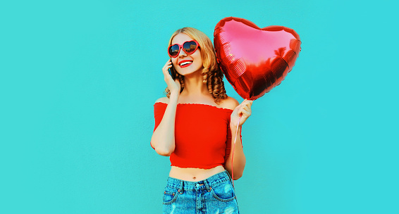 istock Portrait happy smiling woman calling on smartphone holding red heart shaped air balloon on colorful blue background 1202899221