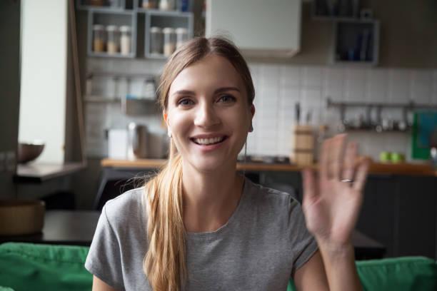 portrait happy smiling woman waving hand, looking at camera - webcam portrait стоковые фото и изображения