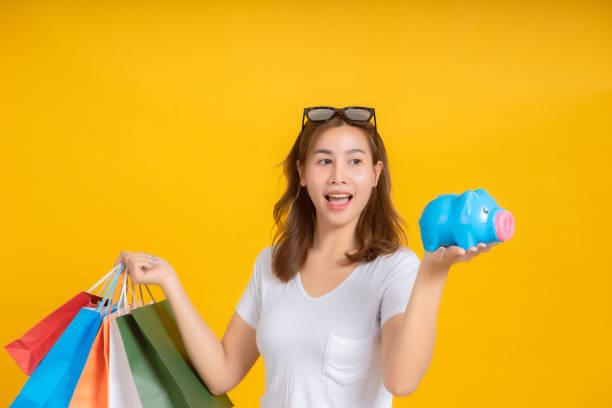 retrato feliz joven mujer asiática sosteniendo piggybank ahorrando dinero para comprar emoción positiva en camiseta blanca, fondo amarillo aislado estudio tiro y copia de espacio. - gerente de cuentas fotografías e imágenes de stock
