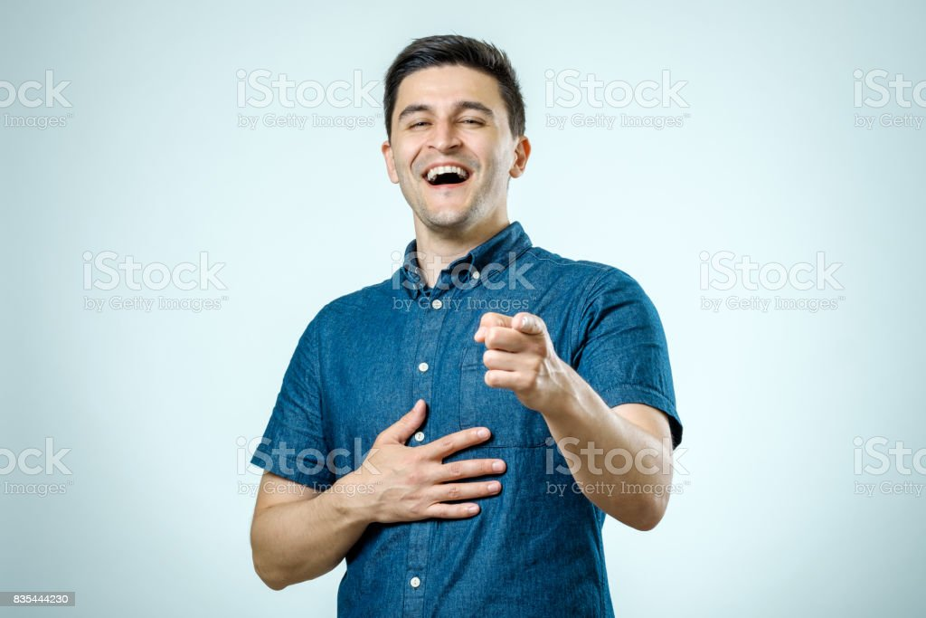 Portrait happy young man, laughing, pointing with finger at someone. Positive human face expressions.  Isolated on gray background stock photo