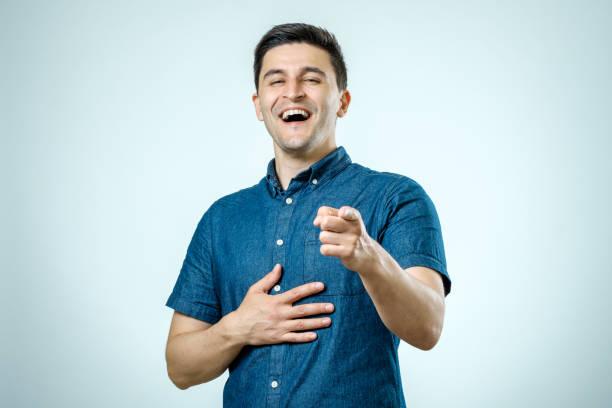 retrato joven hombre feliz, riendo, señalando con el dedo a alguien. expresiones del rostro humano positivo.  aislado sobre fondo gris - ironía fotografías e imágenes de stock
