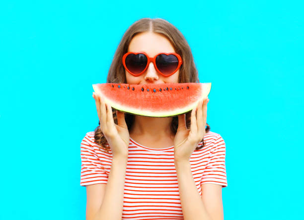 portrait happy young woman is holding slice of watermelon over colorful blue background stock photo