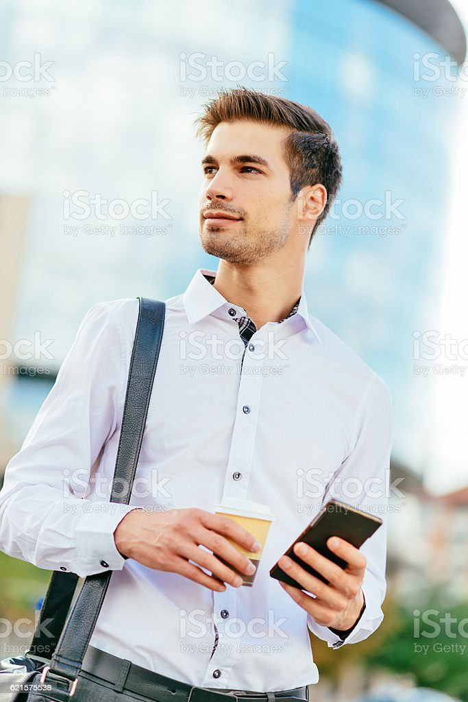 Portrait image of young businessman with phone and coffee photo libre de droits