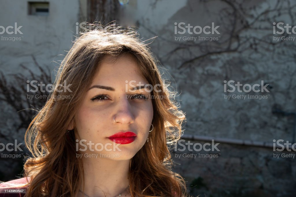 She has red lips, a serious expression, staring at the camera....