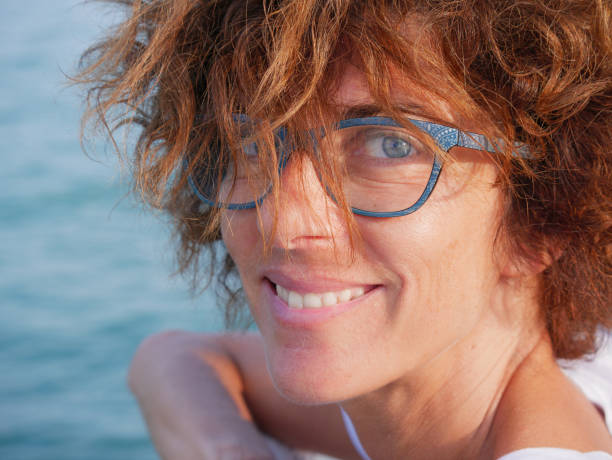 Portrait lady with blue eyes and glasses at sea. Smiling woman on cruise vacation, real people traveling, outdoors natural sunlight, relax city break concept. stock photo