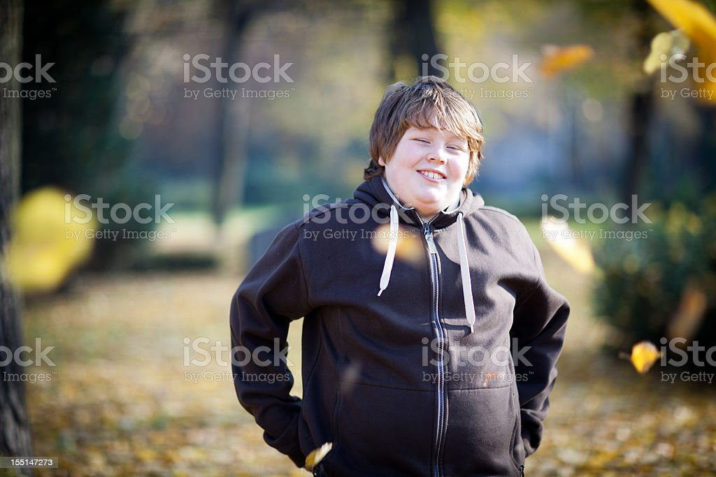 portrait: laughing overweight boy on nature background, looking at camera stock photo