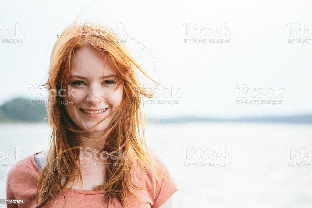 Portrait de Cheveux roux rire jeune femme sur fond de nature - Photo