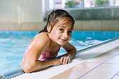 Portrait little girl having fun in indoor swimming-pool. The girl is resting at the water park. Active happy kid. Swimming school for small children. Concept friendly family sport and summer vacation.