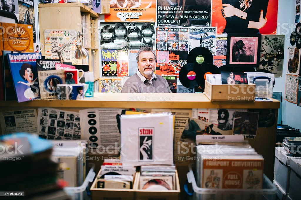 Portrait, man behind checkout counter, vinyl record shop, pop music stock photo