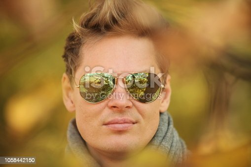 istock portrait man close up among the yellow leaves of an autumn park 1058442150
