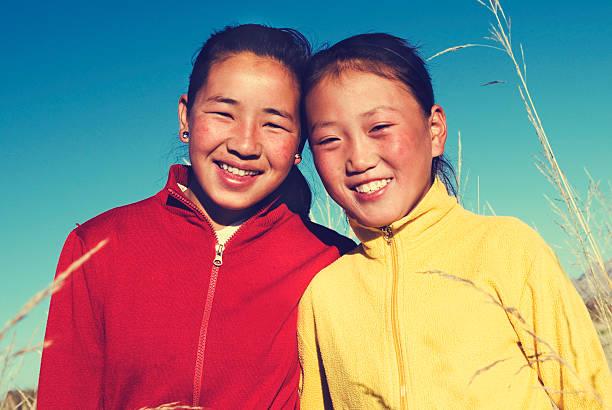 porträt mangolian zwei schwestern schönen lächelnden konzept - rawpixel stock-fotos und bilder