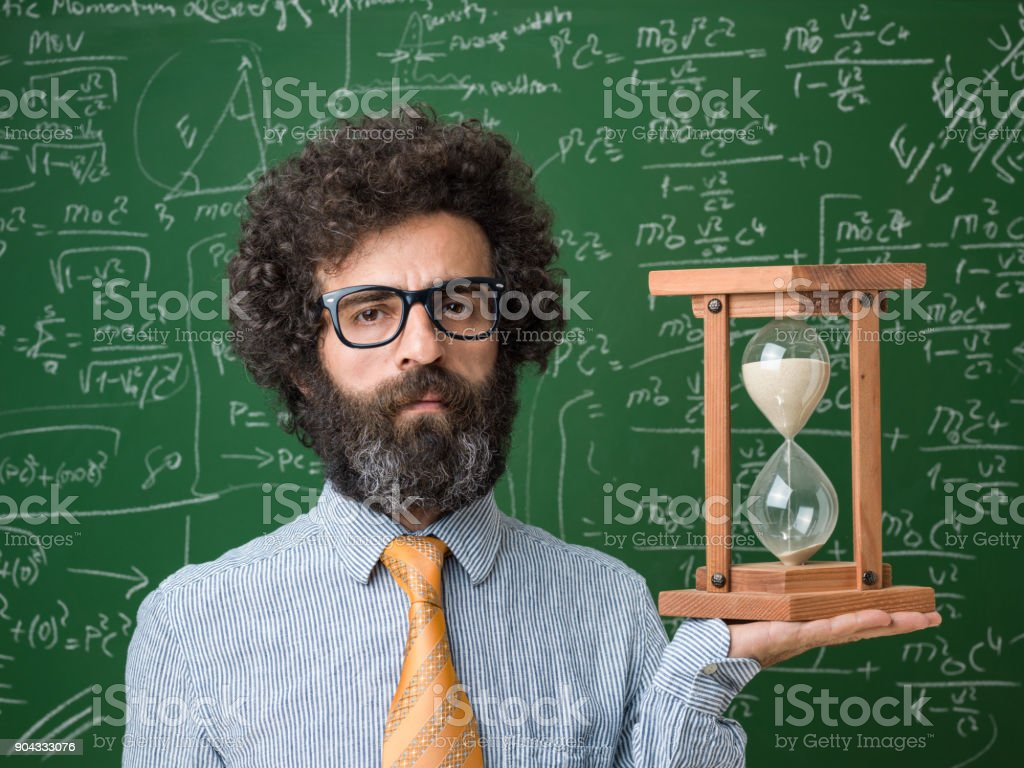 Portrait Mature Adult Scientist Holding Hourglass In Front Of Blackboard stock photo