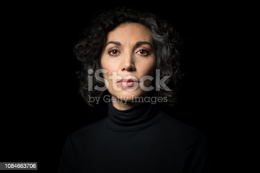 Portrait mature woman staring at camera on black background. Close-up portrait of mature woman  having short curly hair with blank expression.