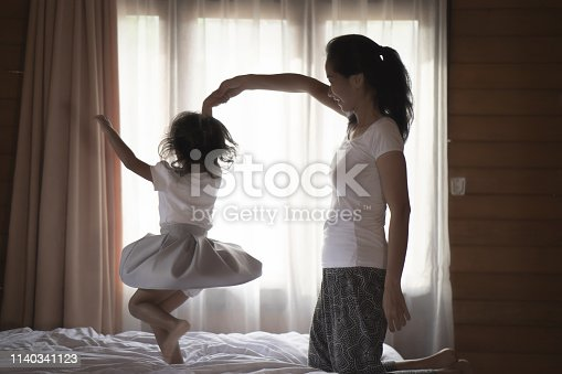 portrait mother and her daughter playing at a bedroom, quality family time