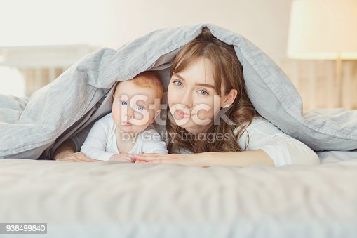 istock Portrait Mother plays with children on the bed 936499840
