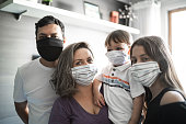 Portrait o family using face mask at home