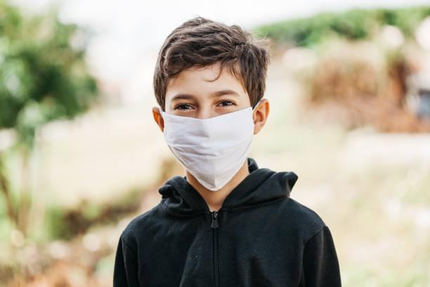 Porträt eines 10-jährigen Jungen, der eine selbstgemachte Schutzmaske trägt, die während der Quarantäne sonnen. Coronavirus, Covid-19 und Pandemie-Konzept – Foto