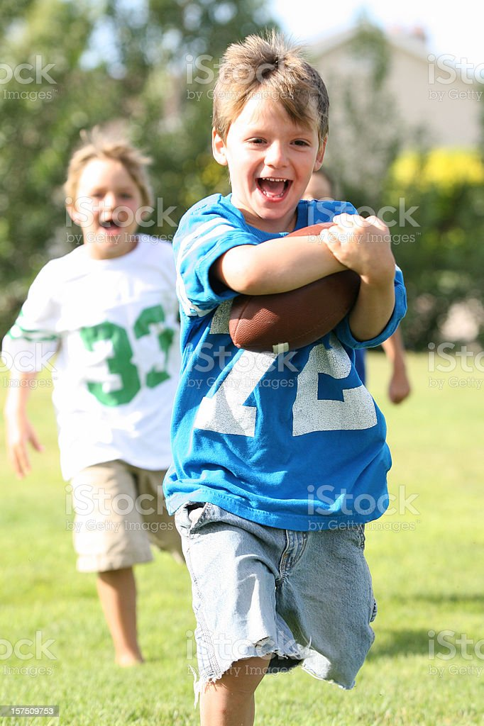 Portrait of 2 young boys running with a football royalty-free stock photo