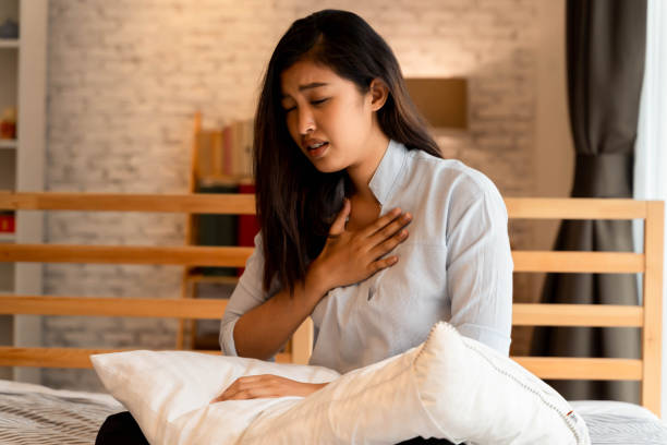 Portrait of 20s young Asian woman having difficulty breathing in bedroom at night. Shortness of breath, asthma, difficult to breathe problems stock photo