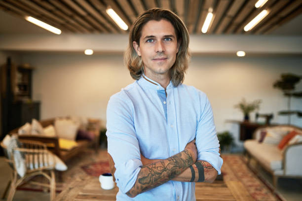 Portrait of 33 Year Old Caucasian Marketing Specialist Close-up of mid adult male marketing freelancer with arms crossed, wearing casual clothing, and looking at camera with contented expression in coworking office. medium length hair stock pictures, royalty-free photos & images