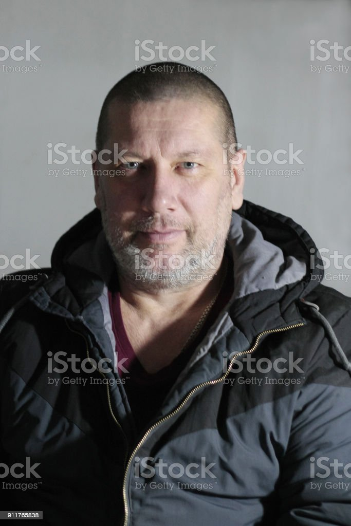 portrait of  40 year old man sitting,close-up on light gray background. stock photo