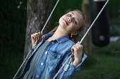 Portrait of a 10 year old schoolgirl with long blonde hair and jeans jacket on a swing smiling at the camera.